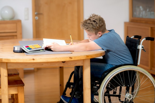boy in wheelchair doing homework