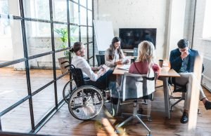 Lavoro e disabilità: young businessman in wheelchair working with colleagues in office