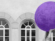 """Due mani che sorreggono in alto una sfera, apparentemente senza sforzo. I colori, verde e viola, sono contrastanti ma funzionali, e riprendono sia il logo di Fed.Man, sia il fatto che la coadiuvazionedi diversità può creare delle sinergie per trasformare le idee in soluzioni in ambito inclusivo (particolare della scultura """"Einwurf zum Spiel"""" (Metti in gioco) di R. Indermaur, foto di F. Nikles)"""""""