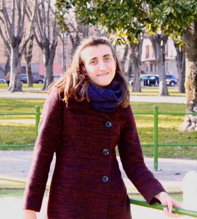 Anida Hilviu in primo piano, a mezzo busto, con alle spalle un parco ed una chioma di un albero