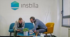 Due businessman seduti nel salottino di un'azienda, mentre guardano una rivista. Alle spalle il logo aziendale: Instilla.